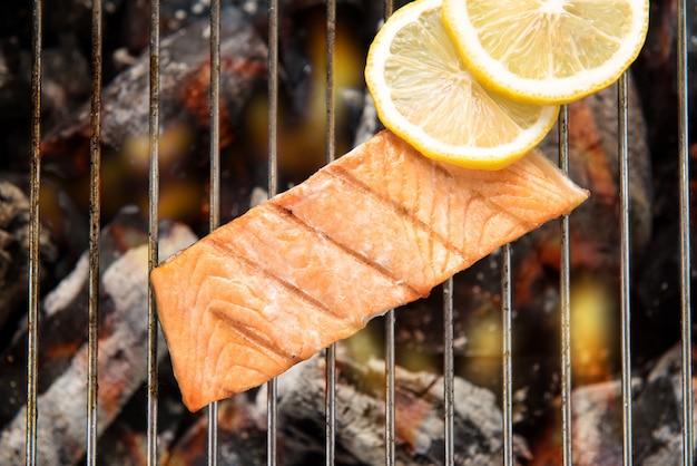 Vue de dessus saumon grillé au citron sur le gril enflammé.