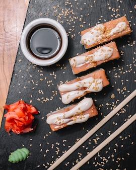 Vue de dessus saumon philadelphia roll avec fromage à la crème nori concombre gingembre wasabi et sauce soja sur une planche