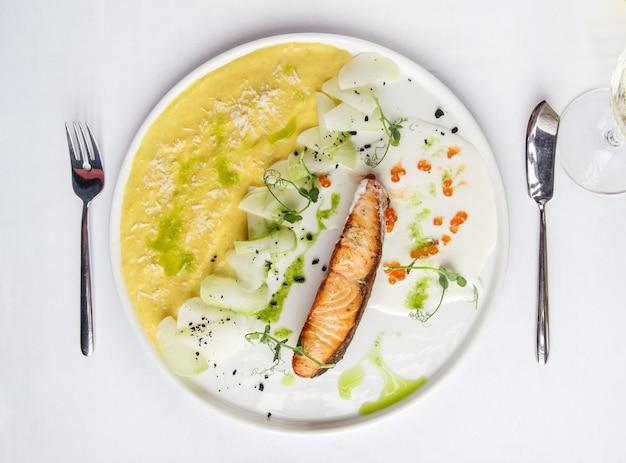 Vue de dessus sur le saumon rôti avec purée de pommes de terre et caviar rouge sur une plaque blanche