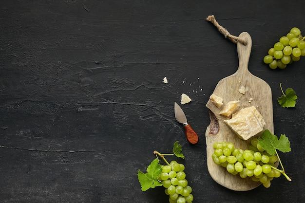 Vue de dessus d'une savoureuse assiette de fromages aux fruits, raisin sur un bureau noir.