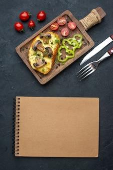 Vue de dessus d'une savoureuse collation faite maison avec des champignons et des légumes hachés sur un cahier de couverts en bois sur fond noir