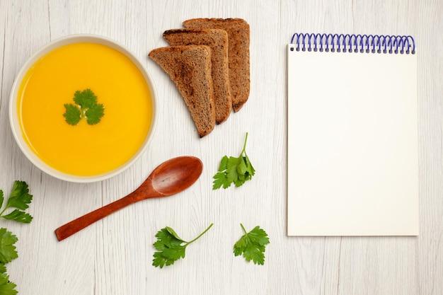 Vue de dessus d'une savoureuse crème de soupe à la citrouille texturée avec des miches de pain noir sur blanc clair