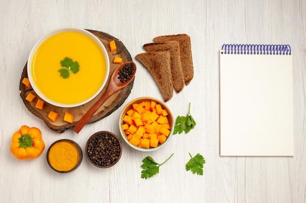 Vue de dessus d'une savoureuse crème de soupe à la citrouille texturée avec des miches de pain noir sur un sol blanc plat de soupe aux légumes sauce repas