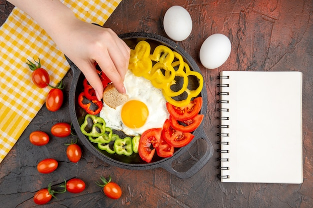 Vue de dessus savoureuse omelette aux tomates et poivrons tranchés sur la table sombre
