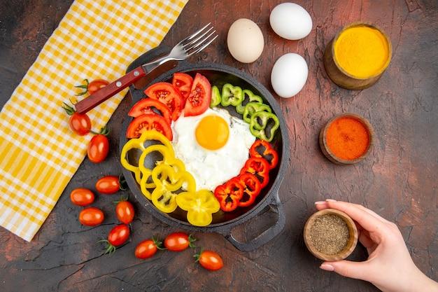 Vue de dessus savoureuse omelette avec des poivrons tranchés et des assaisonnements sur la table sombre