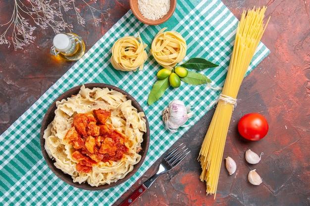 Vue de dessus savoureuse pâte cuite avec du poulet et de la sauce sur un plat de pâtes de couleur foncée