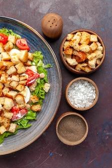 Vue de dessus savoureuse salade césar avec assaisonnements sur le bureau sombre