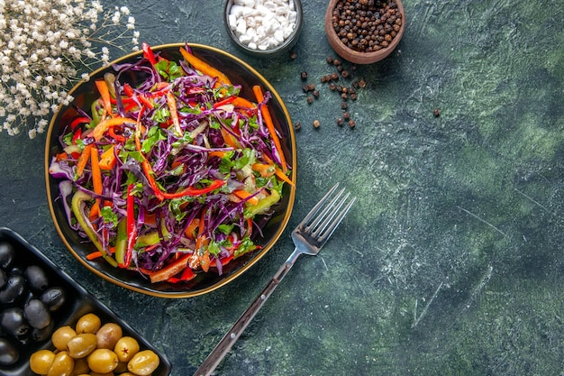 Vue de dessus savoureuse salade de chou avec des poivrons à l'intérieur de la plaque sur fond sombre repas santé pain snack régime alimentaire de vacances