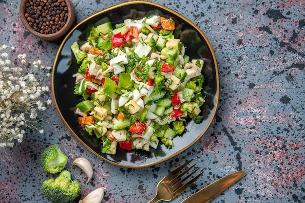 Vue de dessus savoureuse salade de légumes avec des couverts sur fond sombre nourriture restaurant couleur alimentation santé cuisine mûre