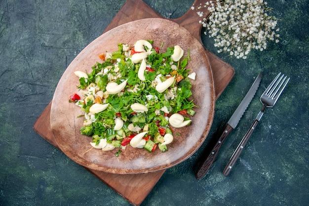 Vue de dessus savoureuse salade de légumes à l'intérieur de la plaque avec des couverts sur fond bleu foncé cuisine couleur santé ajustement dîner cuisine diète déjeuner repas restaurant