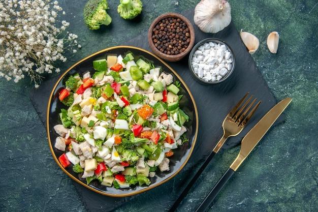 Vue de dessus savoureuse salade de légumes à l'intérieur de la plaque avec des couverts sur fond bleu foncé cuisine restaurant repas frais santé déjeuner couleur de l'alimentation