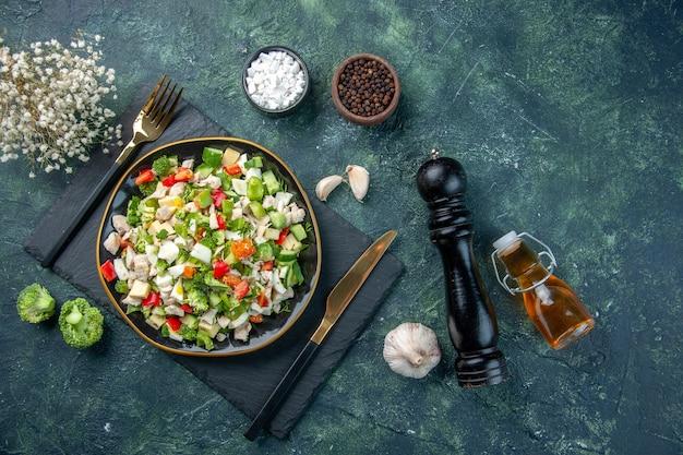 Vue de dessus savoureuse salade de légumes à l'intérieur de la plaque sur le fond bleu foncé cuisine restaurant repas frais couleur santé déjeuner régime alimentaire