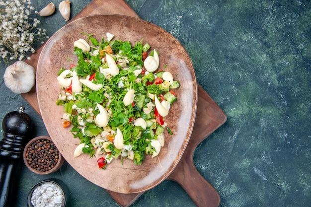Vue de dessus savoureuse salade de légumes à l'intérieur de la plaque sur un fond bleu foncé restaurant cuisine dîner déjeuner santé fit cuisine couleurs repas
