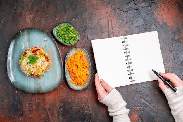 Vue de dessus savoureuse salade de légumes à l'intérieur de la plaque avec des verts et des carottes sur une table sombre