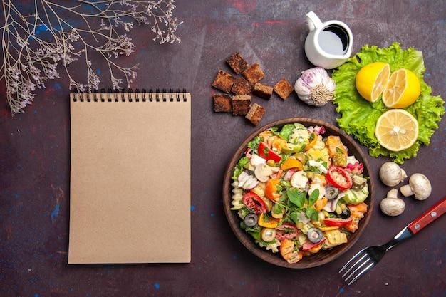 Vue de dessus d'une savoureuse salade de légumes avec des tranches de citron frais sur fond noir