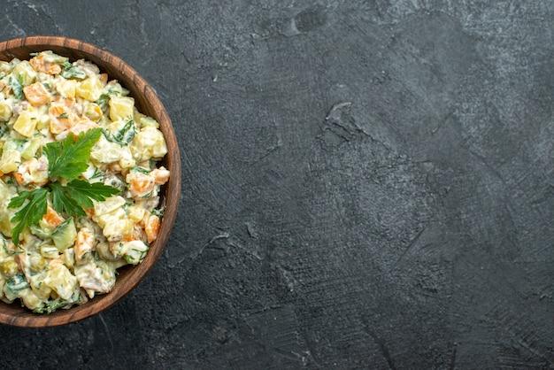Vue de dessus savoureuse salade mayyonaise à l'intérieur de la plaque brune sur fond noir