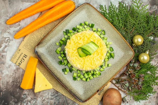 Vue de dessus d'une savoureuse salade servie avec du concombre haché sur un vieux journal