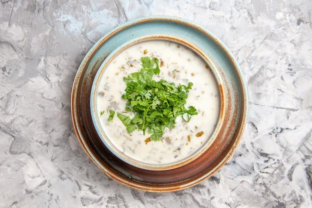 Vue de dessus savoureuse soupe au yogourt dovga avec des verts à l'intérieur de la plaque sur table blanche repas de soupe au lait