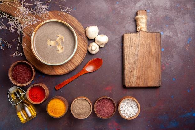 Vue de dessus savoureuse soupe aux champignons avec différents assaisonnements sur le fond sombre soupe aux champignons assaisonnement repas alimentaire