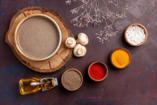 Vue de dessus savoureuse soupe aux champignons avec différents assaisonnements sur fond violet foncé assaisonnements pour soupe repas alimentaire