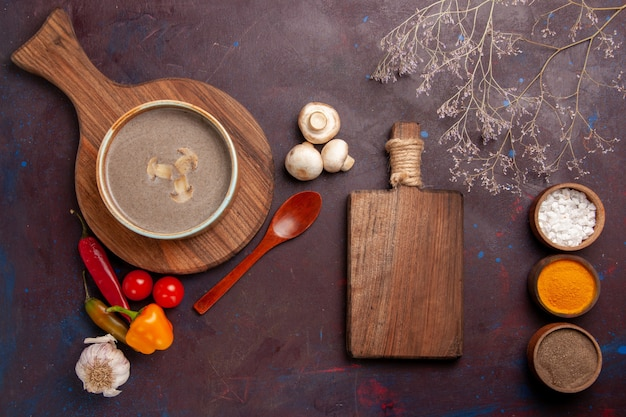 Vue de dessus savoureuse soupe aux champignons avec différents assaisonnements sur le sombre bureau soupe assaisonnement aux champignons repas alimentaire