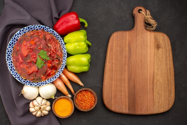 Vue de dessus savoureuse soupe de betterave ukrainienne au bortsch avec des légumes frais sur l'espace sombre