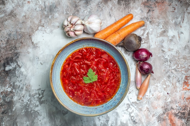 Vue de dessus de la savoureuse soupe de betterave ukrainienne bortsch avec des légumes frais sur une surface sombre