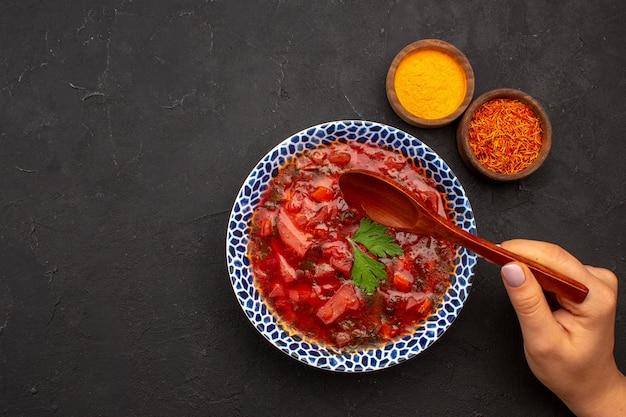 Vue de dessus savoureuse soupe de betteraves ukrainienne au bortsch avec assaisonnements sur un espace sombre