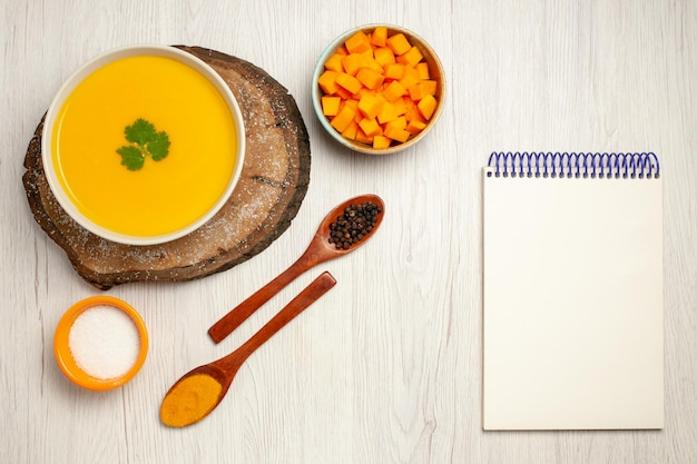 Vue de dessus d'une savoureuse soupe à la citrouille avec assaisonnements et bloc-notes sur blanc