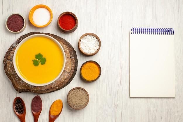 Vue de dessus d'une savoureuse soupe à la citrouille avec différents assaisonnements sur blanc
