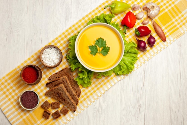 Vue de dessus d'une savoureuse soupe à la citrouille avec différents assaisonnements et pain sur blanc
