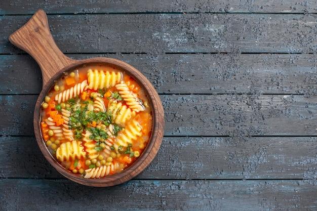 Vue de dessus savoureuse soupe de pâtes à partir de pâtes italiennes en spirale avec des verts sur le plat de cuisine de pâtes italiennes de couleur de soupe de bureau bleu foncé