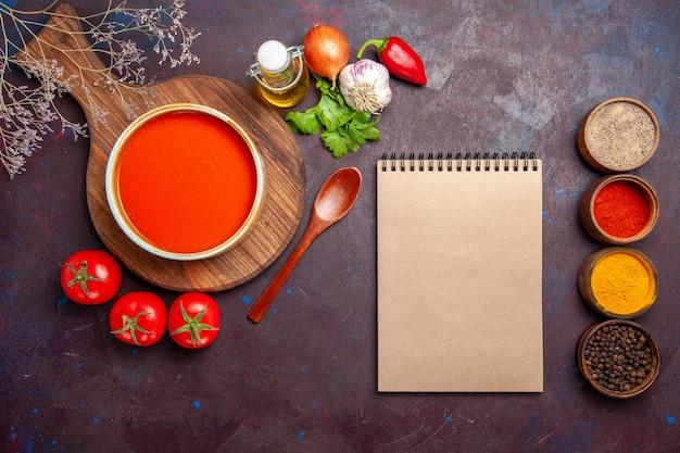 Vue de dessus d'une savoureuse soupe de tomates avec des assaisonnements et des tomates fraîches sur une table sombre