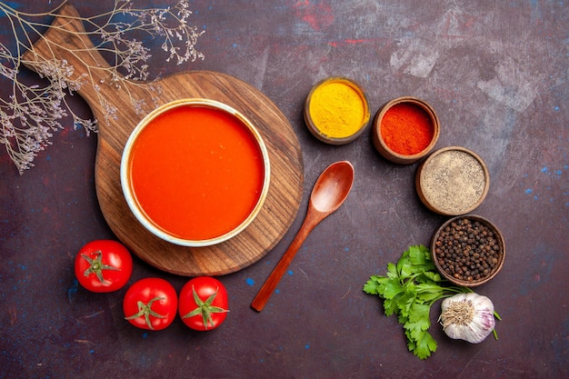 Vue de dessus d'une savoureuse soupe de tomates avec des tomates fraîches et des assaisonnements sur noir