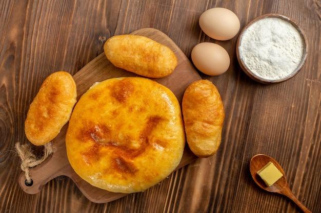 Vue de dessus savoureuse tarte à la citrouille avec des petits pains aux pommes de terre sur le bureau en bois marron gâteau à la tarte au four à gâteaux