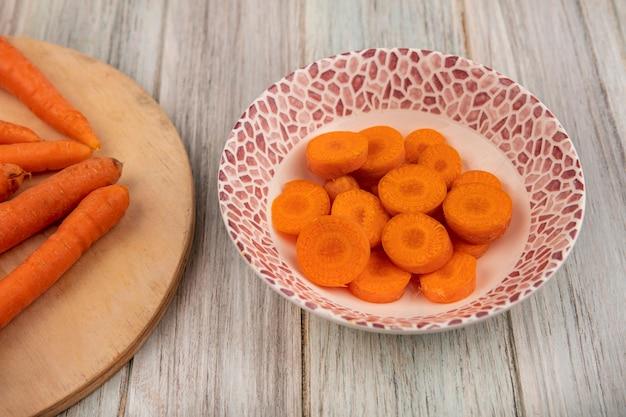 Vue de dessus de savoureuses carottes hachées orange sur un bol sur un mur en bois gris