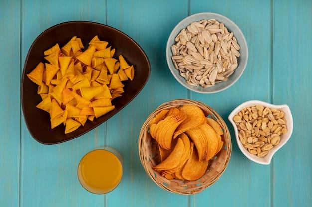 Vue de dessus de savoureuses chips croustillantes sur un seau avec des graines de tournesol blanches sur un bol avec des pignons de pin avec un verre de jus d'orange