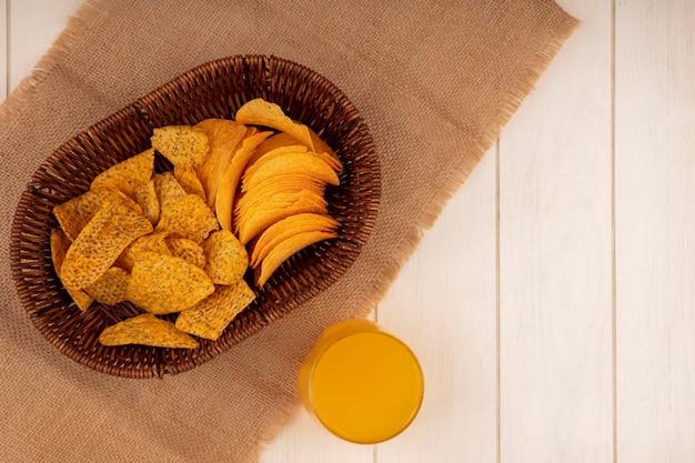 Vue de dessus de savoureuses chips croustillantes sur un seau sur un sac en tissu avec un verre de jus d'orange sur une table en bois beige avec espace copie