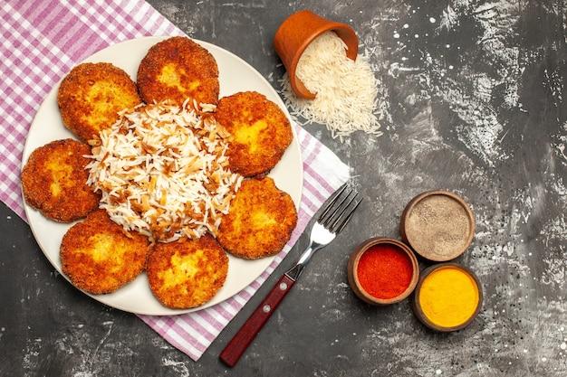 Vue de dessus de savoureuses côtelettes frites avec du riz cuit sur un plat de viande de rissole au sol sombre