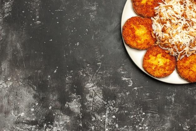 Vue de dessus de savoureuses côtelettes frites avec du riz cuit sur une surface sombre repas plat de viande photo
