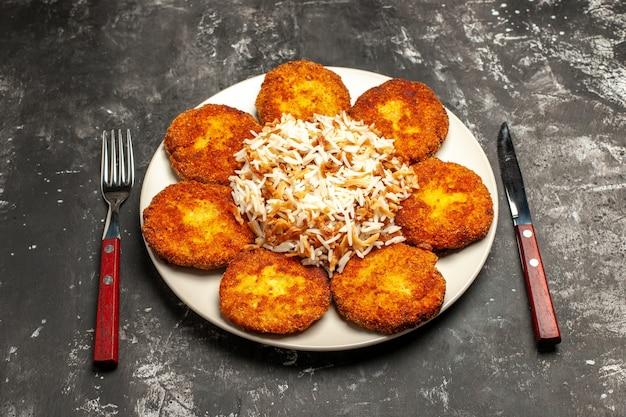 Vue de dessus de savoureuses côtelettes frites avec du riz cuit sur la viande de repas de plat photo surface sombre