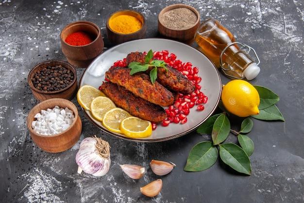 Vue de dessus de savoureuses côtelettes de viande avec assaisonnements sur plat de nourriture de repas de bureau gris