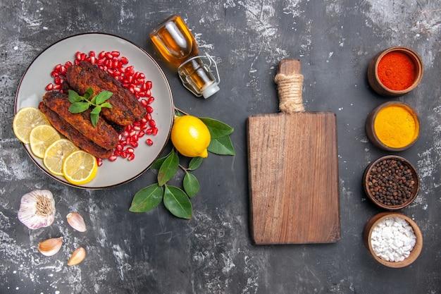 Vue de dessus de savoureuses côtelettes de viande avec assaisonnements sur le plat de nourriture repas fond gris