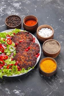 Vue de dessus de savoureuses côtelettes de viande avec salade fraîche sur un bureau gris