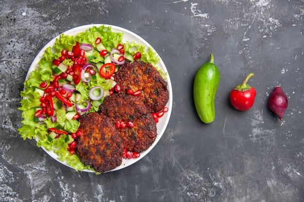 Vue de dessus de savoureuses côtelettes de viande avec salade fraîche sur fond gris photo plat alimentaire viande