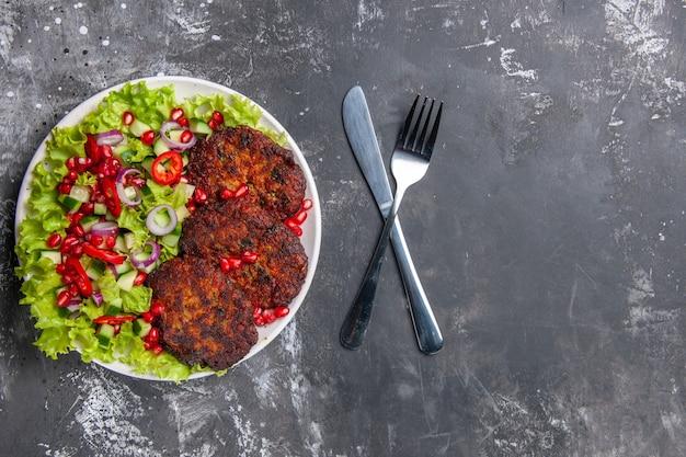 Vue de dessus de savoureuses côtelettes de viande avec salade fraîche sur fond gris photo plat de viande nourriture