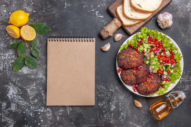 Vue de dessus de savoureuses côtelettes de viande avec salade et pain sur le plat de fond gris repas photo