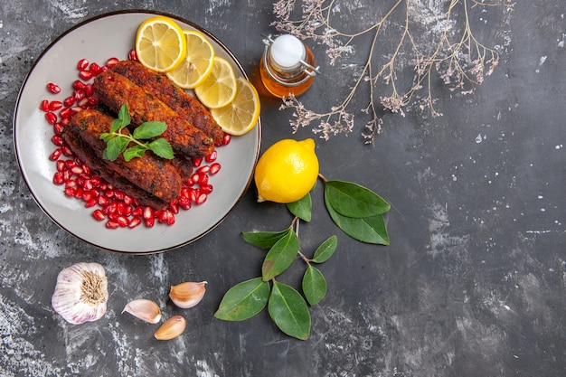 Vue de dessus de savoureuses côtelettes de viande avec des tranches de citron sur le fond gris plat photo alimentaire