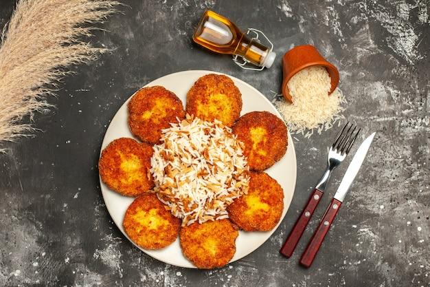 Vue de dessus de savoureuses escalopes frites avec du riz cuit sur un plat de surface sombre