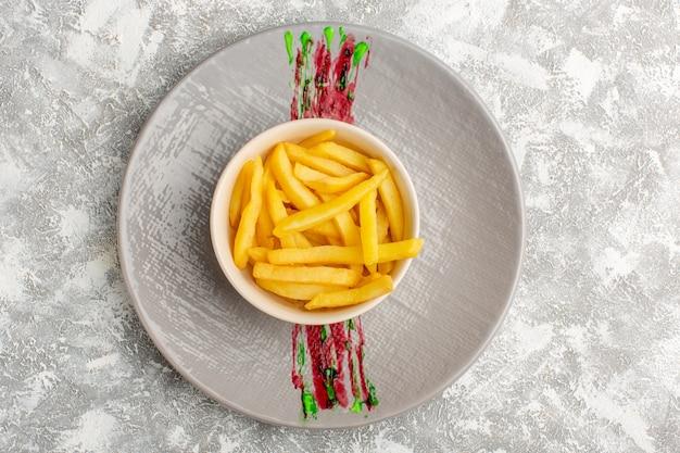 Vue de dessus de savoureuses frites à l'intérieur d'une plaque blanche sur la surface lumineuse